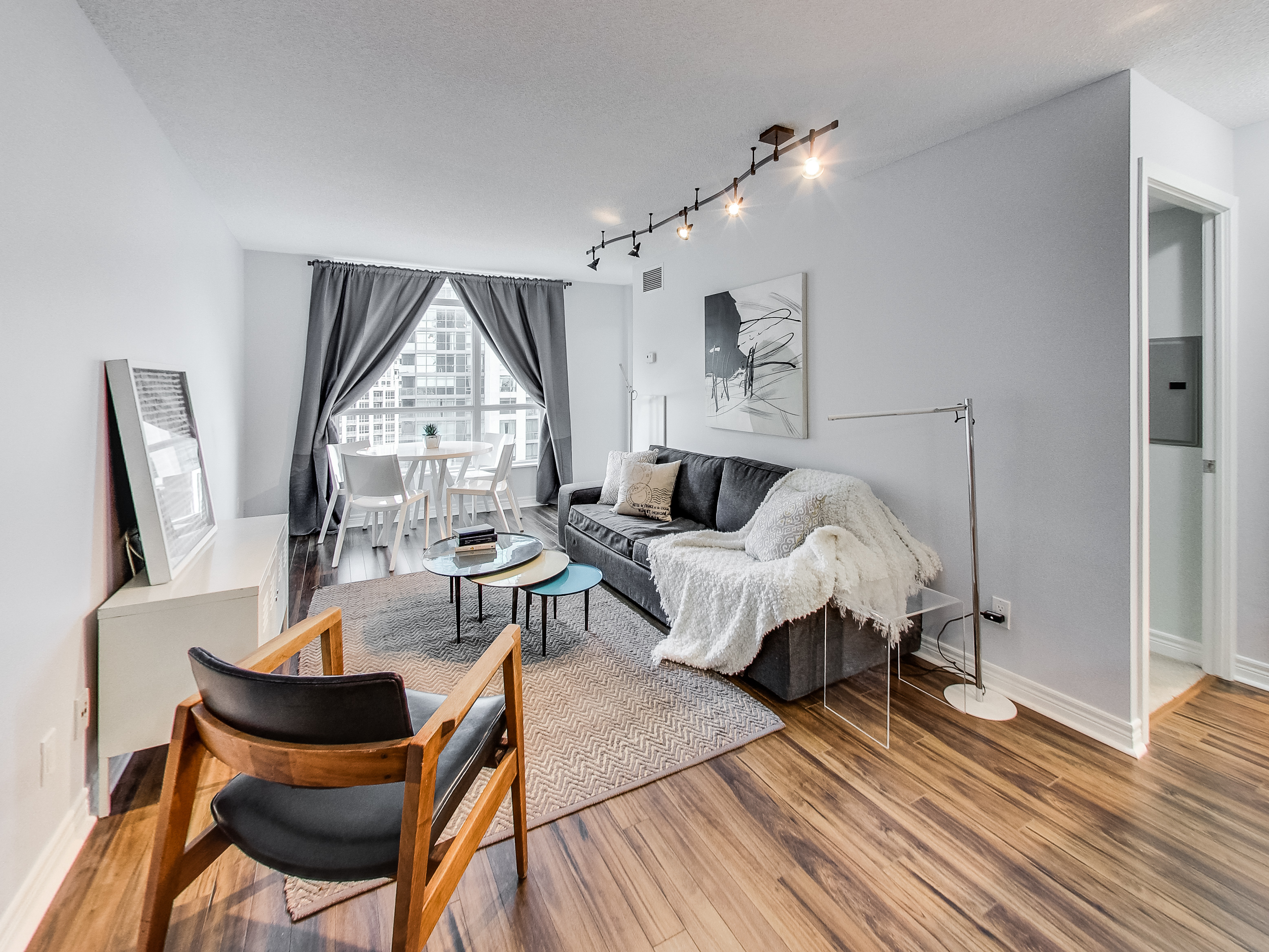 living room with cozy couch, wooden flooring, carpet, small balcony